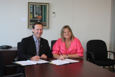 Former Minister of the Department of Human Resources Troy Lifford and NBU President Susie Proulx-Daigle sign a collective bargaining agreement.